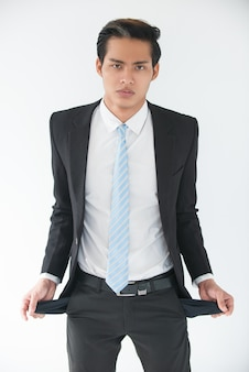 Upset young businessman showing empty pockets