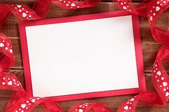 Valentine card with a red ribbon on a wooden table