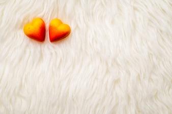 Valentine theme: Heart-shaped chocolate on fur texture.