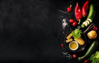 Various vegetables on a black table with space for a message