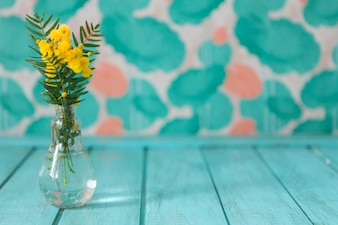 Vase with flowers on blue wooden surface