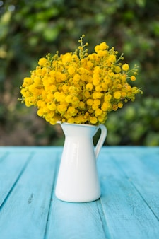 Vase with yellow flowers on blue surface