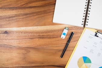 View from above of office supplies and   analyze business chart on a wooden working table background.