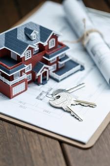 Villa house model, key and drawing on retro desktop (real estate sale concept)