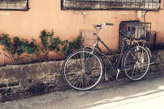 Vintage bicycle parked at old wall in the urban narrow street (vintage color tone styles)