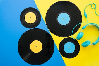 Vinyls and headphones on blue and yellow background