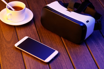 Vr glasses and cell phone on wooden desk