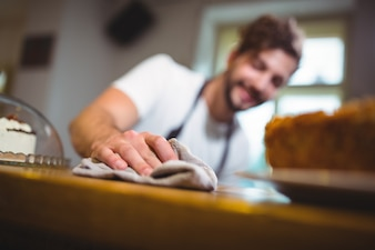 Waiter wiping counter with napkin in café