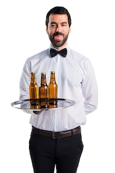 Waiter with beer bottles on the tray doing a joke