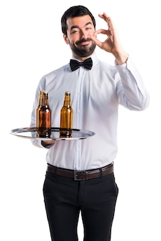 Waiter with beer bottles on the tray making OK sign