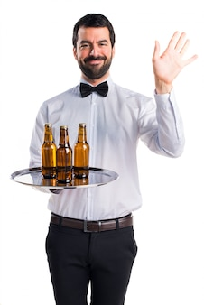 Waiter with beer bottles on the tray saluting