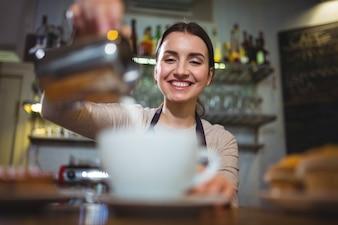 ウェイトレスカフェカウンターでコーヒーを作ります