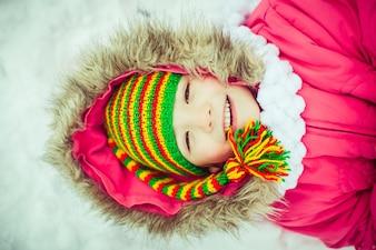 Warm girl lying in the snow