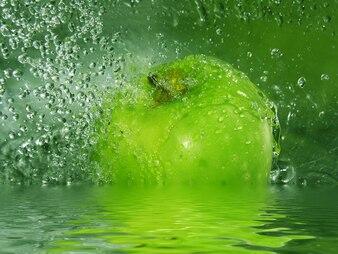 Water splashing on a green apple