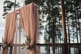 ピンクの布とバラで作られた結婚式の祭壇