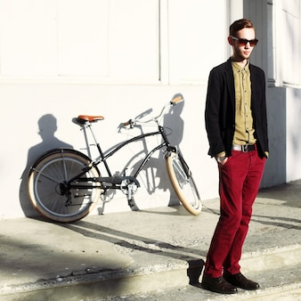 Well-dressed teen posing with bicycle in the city