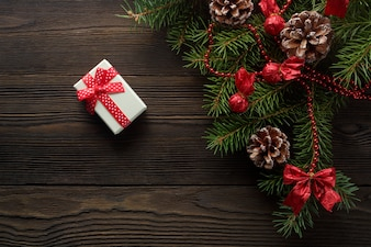 White box with a red bow on a wooden table with christmas ornament