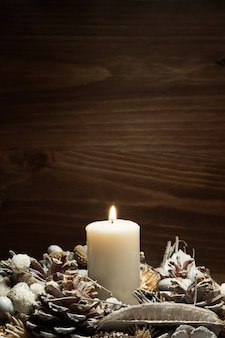 White candle lit with pine cone ornaments