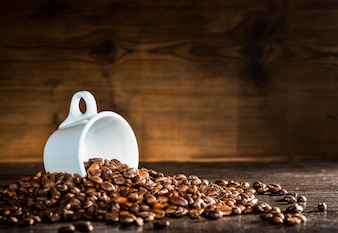 White cup surrounded by coffee beans