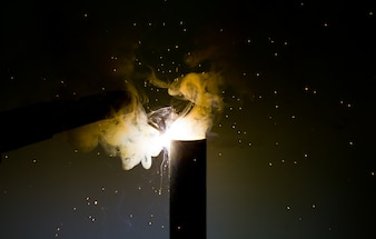White hot sparks and white smoke at grinding steel material