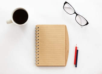 White office desk with a notebook and pencils, glasses
