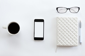 White office desk with glasses, mobile phone, coffee and pen