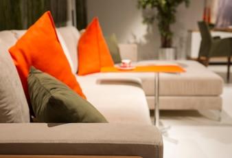 White sofa with orange cushions