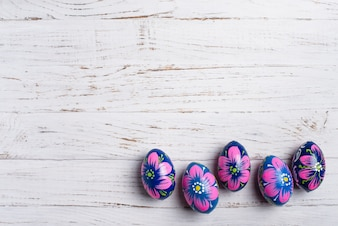 White wooden surface with four blue and pink easter eggs