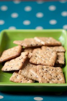 Whole grains biscuits on green plate and polka dot table