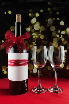 Wine bottle with a red ribbon and two empty glasses with bokeh effect
