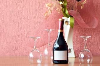 Бокал для вина и бутылка на деревянном столе