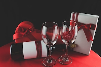 Wine glasses with a heart inside a gift and a box of chocolates