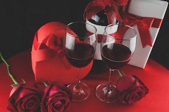 Wine glasses with romantic decoration and gifts seen from above