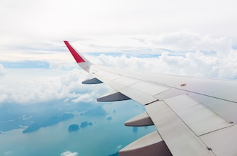 Wing of an airplane flying above sea and island