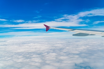 Wing of an airplane flying above the clouds .