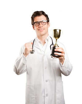 Winner doctor with a gold cup against white background