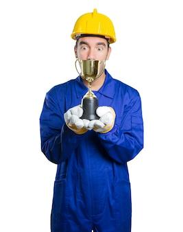白い背景に金の杯を持っている勝者の労働者