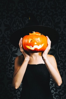 Witch covering face by pumpkin