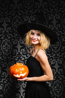 Witch with pumpkin smiling at camera