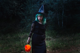 Witch woman with pumpkin in forest