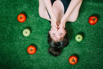 Woman amidst apples and tomatoes
