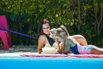 Woman and girl lying poolside reading books