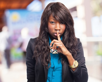 Woman asking for silence with a finger on her lips