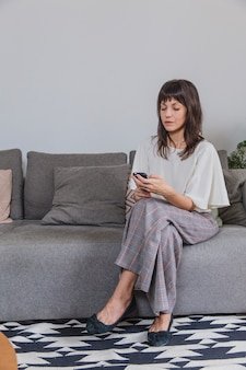 Woman at home on sofa with smartphone