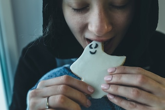 Woman biting ghost cookie