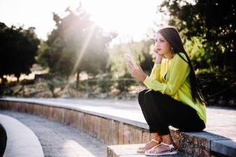 Woman browsing smartphone on steps
