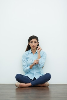 Woman Buttoning on Cuff and Sitting on Floor