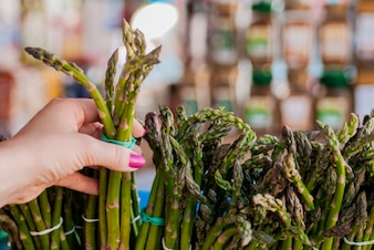 Woman buys asparagus. Bunch of fresh asparagus with woman hands.  woman holding showing asparagus in closeup. Healthy eating concept