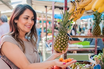 Woman choosing pineapple during shopping at fruit vegetable green market. Attractive woman shopping. beautiful young woman picking up, choosing fruits, pineapples.