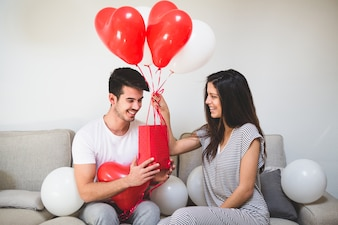 Woman delivering her boyfriend balloons and a red bag
